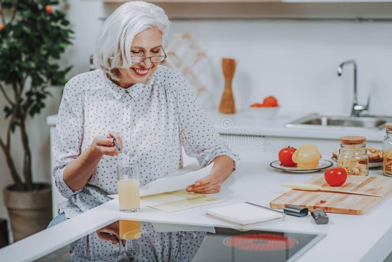 A senhora envelhecida alegre está lendo a receita antes de cozinhar em casa foto de stock