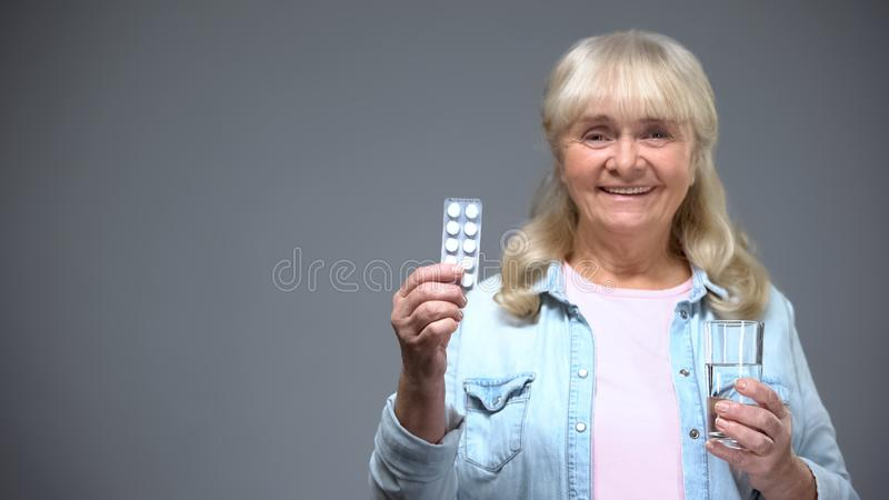 Senhora envelhecida de sorriso que mostra a qualidade da medicamenta??o dos comprimidos, imunidade que refor?a drogas fotografia de stock royalty free