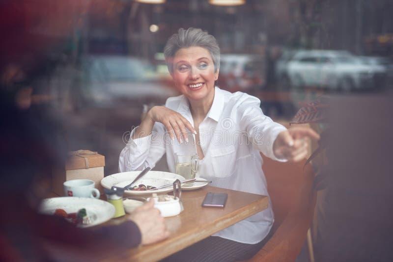 Senhora envelhecida feliz que aponta fora do assento no café fotografia de stock