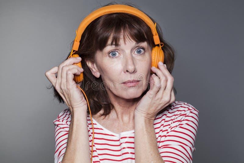 Senhora envelhecida meio que puxa o fones de ouvido longe da orelha imagem de stock