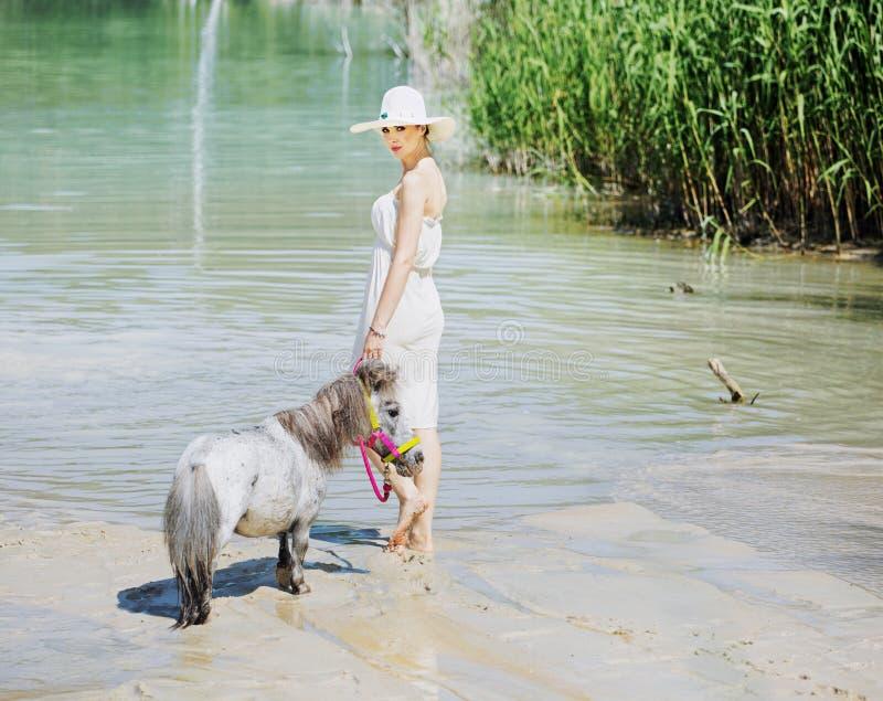 Senhora esperta que anda com o cavalo pequeno imagens de stock royalty free