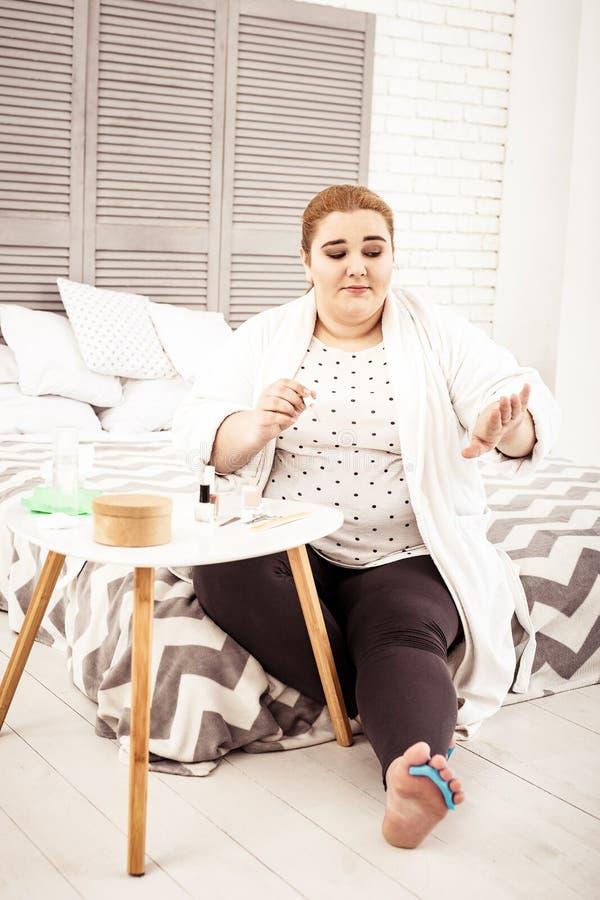 Senhora excesso de peso do gengibre que verifica seu tratamento de mãos ao sentar-se na cama fotos de stock royalty free
