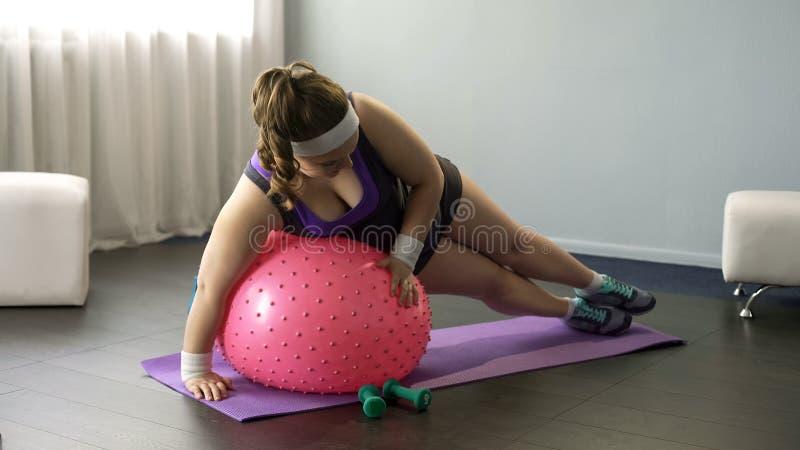 Senhora excesso de peso que tenta fazer exercícios na bola da aptidão, fazendo tentativas engraçadas foto de stock