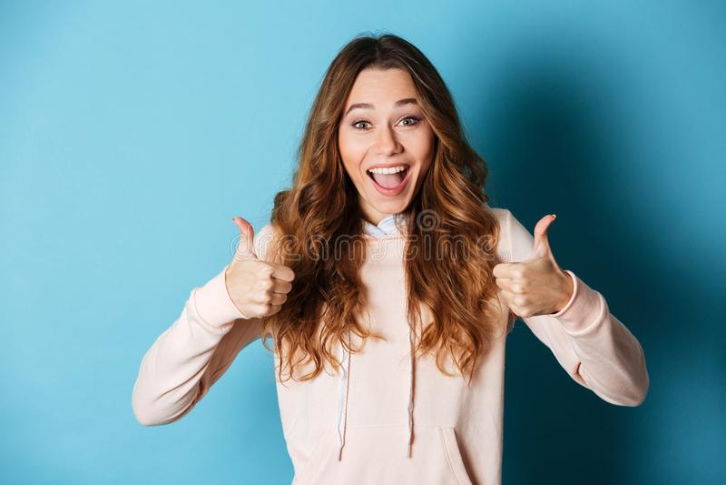 Senhora feliz bonito que mostra os polegares acima fotografia de stock royalty free