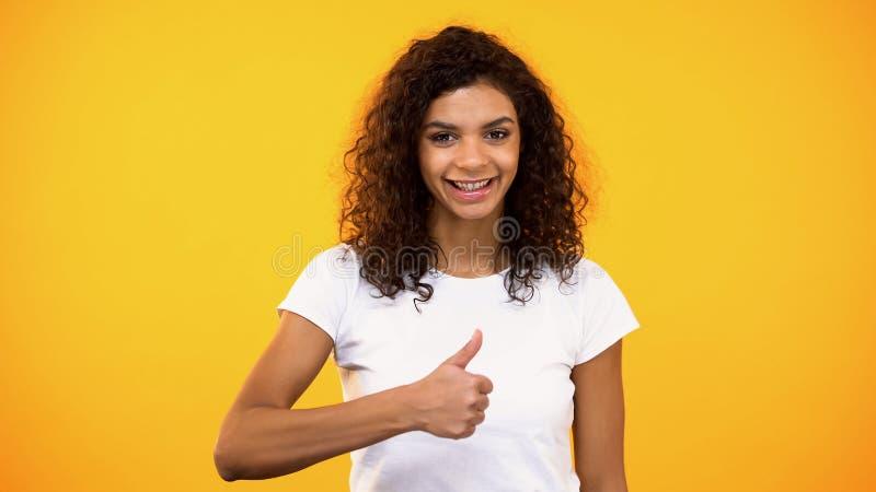 Senhora feliz da misturado-raça que mostra os polegares acima na câmera, reação positiva, aprovação imagem de stock