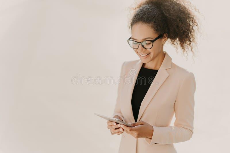 A senhora feliz do negócio está com touchpad, lê a notícia em linha, veste espetáculos e a roupa elegante, tem o cabelo encaracol fotos de stock royalty free