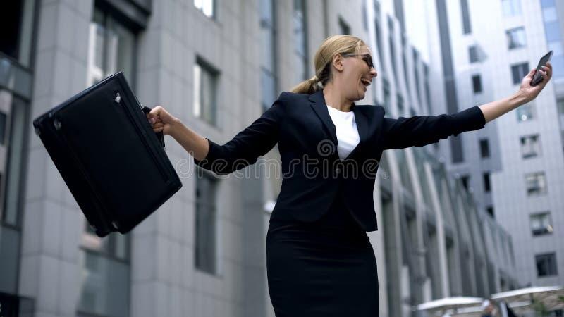 Senhora feliz do negócio que dança alegremente após ter lido o email sobre a promoção, trabalho imagens de stock royalty free