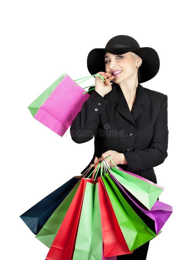 Senhora feliz em um terno de negócio e em um chapéu, sacos de compras de papel fotografia de stock royalty free