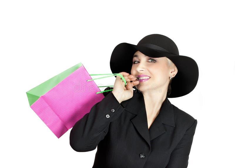 Senhora feliz em um terno de negócio e em um chapéu, um saco de papel foto de stock royalty free
