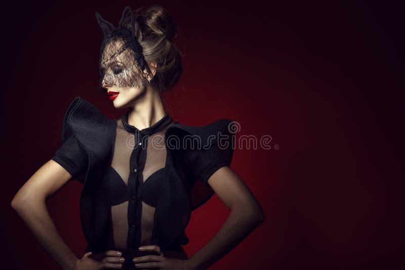 A senhora fino com cabelo do updo e perfeitos lindos compõem o bodysuit vestindo do laço com as luvas do folho e a máscara preta  foto de stock