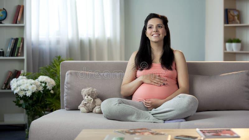 Senhora grávida inspirada que afaga a barriga, sonhando o mais logo da aparência de recém-nascido fotografia de stock royalty free
