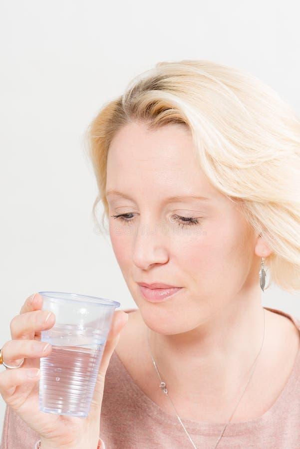 Senhora Holding e vista do copo plástico com água fotografia de stock