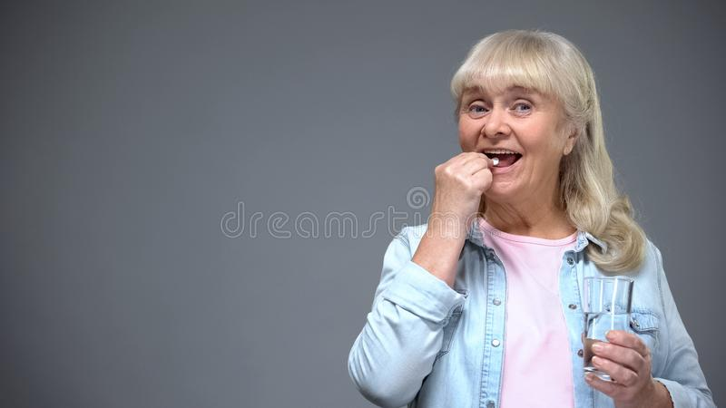 Senhora idosa alegre que toma o comprimido antiviroso, imunidade que refor?a, cuidados m?dicos foto de stock royalty free