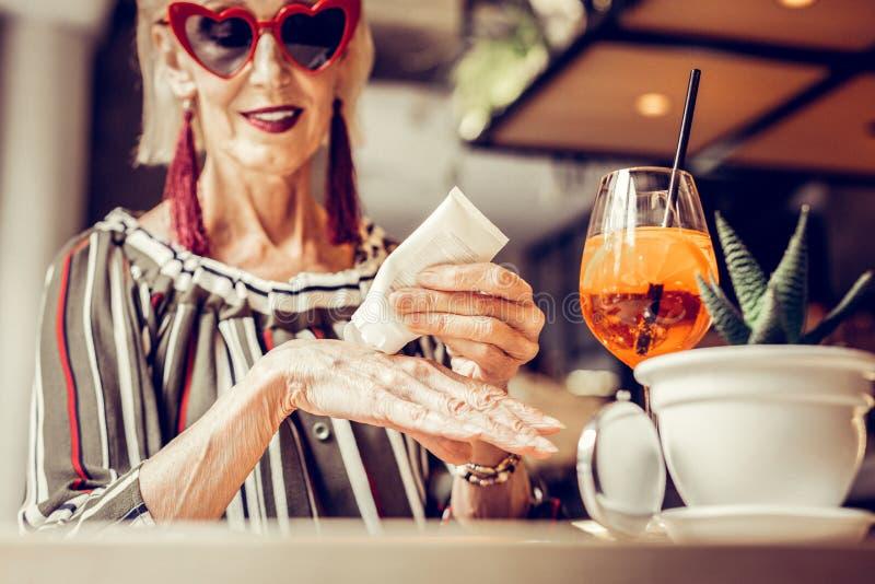 Senhora idosa bonita atenta com a joia longa que espreme o produto imagens de stock royalty free