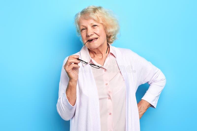 Senhora idosa bonita no revestimento branco do laboratório que guarda vidros e que loooking na câmera imagens de stock
