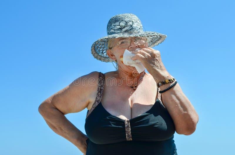 Senhora idosa com chapéu que come a filhós fotografia de stock
