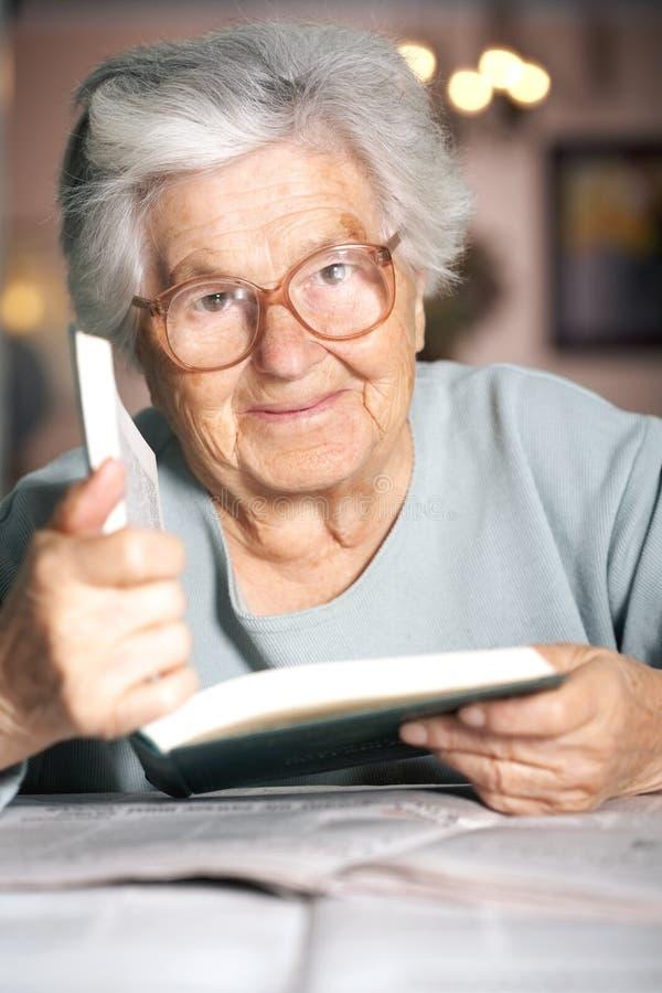 Senhora idosa com um livro fotografia de stock royalty free