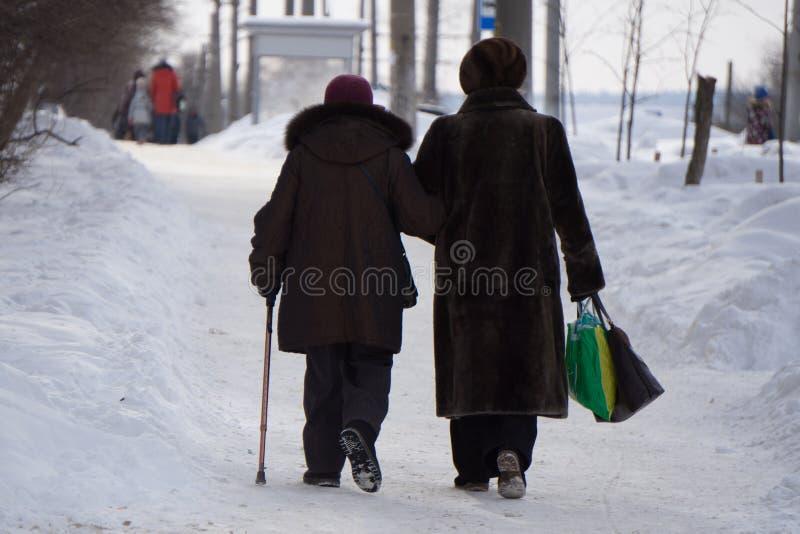 Senhora idosa com uma vara de passeio que fala a uma fêmea em um passeio do beira-mar foto de stock royalty free