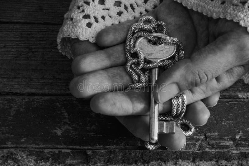 A senhora idosa da forma guarda uma chave dourada em suas mãos foto de stock