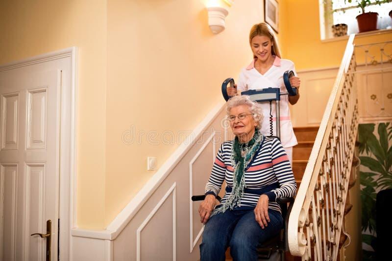 Senhora idosa de sorriso, feliz quando a enfermeira a ajudar a escalar ao st fotos de stock royalty free