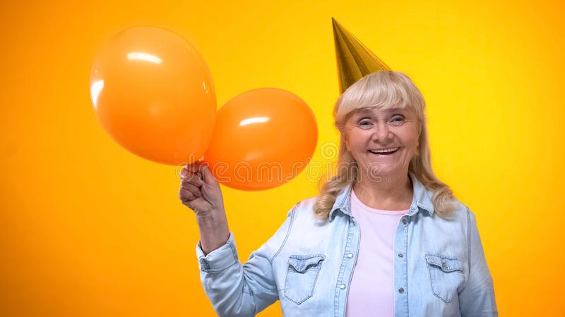 Senhora idosa de sorriso feliz que guarda balões no fundo amarelo, aniversário imagens de stock