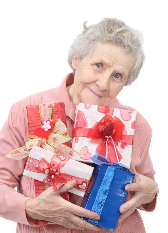 Senhora idosa e caixas com presentes fotografia de stock