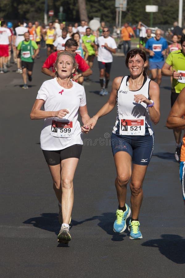 Senhora idosa e mulher que correm guardando a mão Competição de esporte imagens de stock royalty free