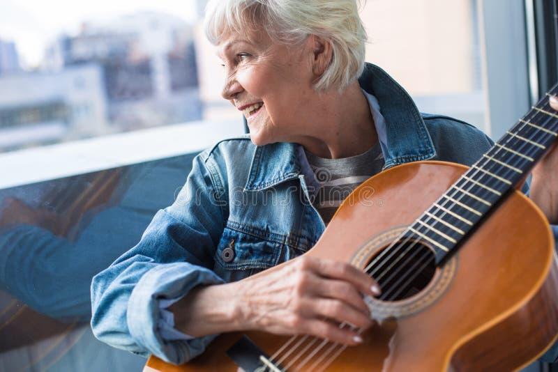 Senhora idosa elegante que guarda o instrumento musical ao sentar-se na janela imagem de stock