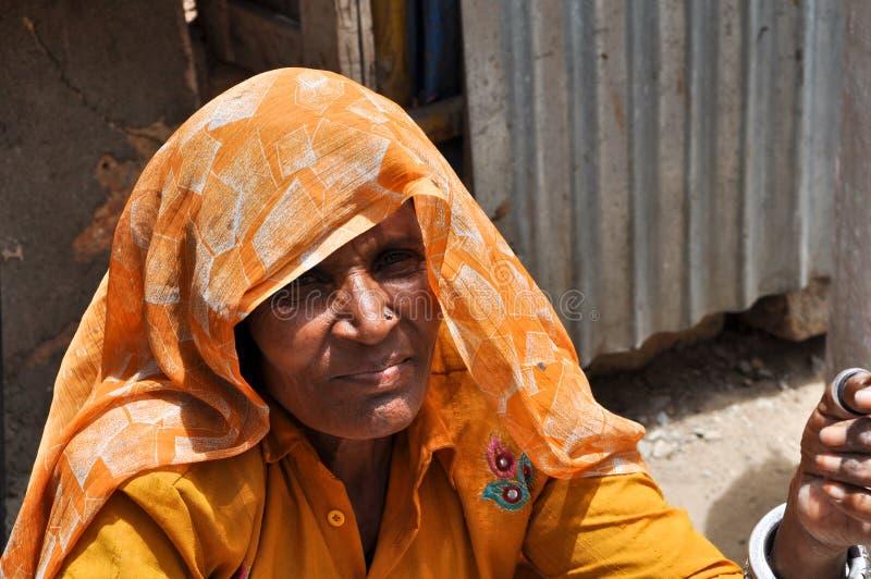 Senhora idosa em India que faz braceletes do encanto foto de stock royalty free