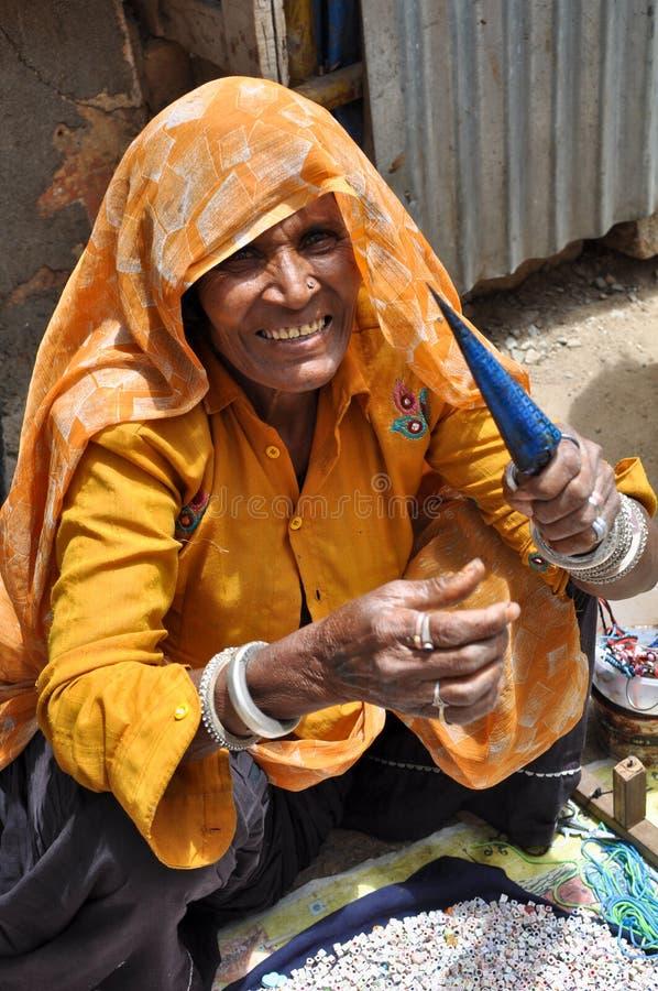 Senhora idosa em India que faz braceletes do encanto imagens de stock royalty free