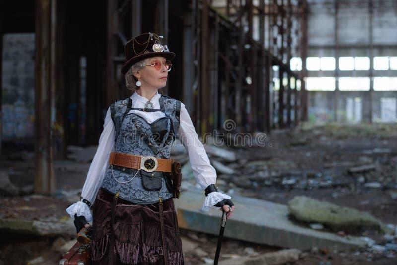 Senhora idosa em um traje do steampunk em uma f?brica abandonada com bra?os ? disposi??o imagem de stock