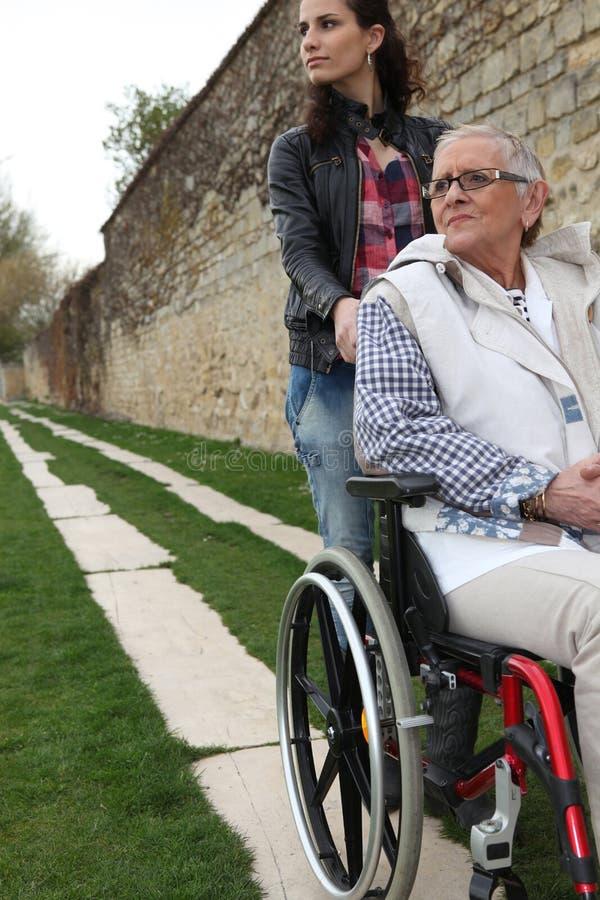 Senhora idosa em uma cadeira de rodas fotografia de stock royalty free