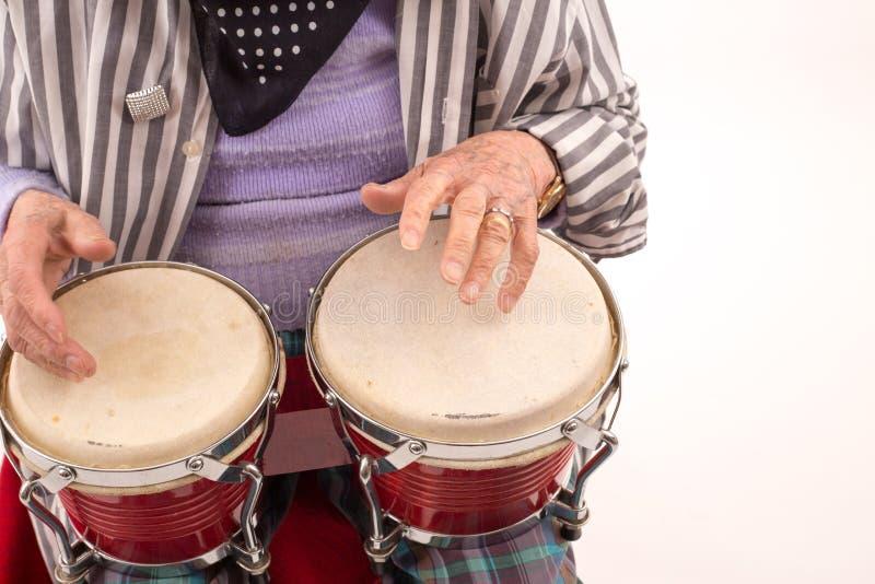 Senhora idosa engraçada que joga bongos imagens de stock