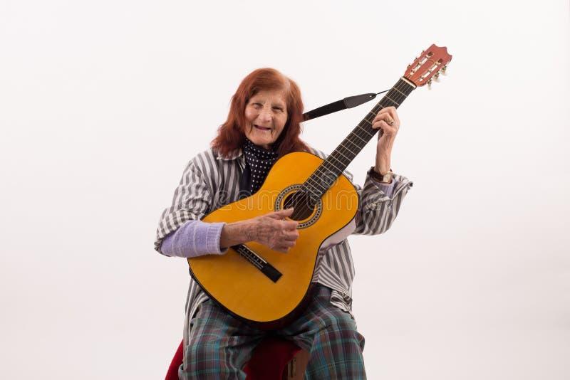 Senhora idosa engraçada que joga a guitarra acústica imagens de stock royalty free