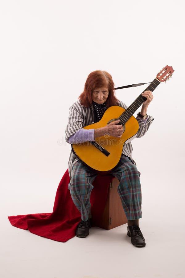 Senhora idosa engraçada que joga a guitarra acústica imagens de stock