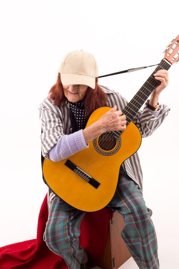 Senhora idosa engraçada que joga a guitarra acústica fotos de stock royalty free