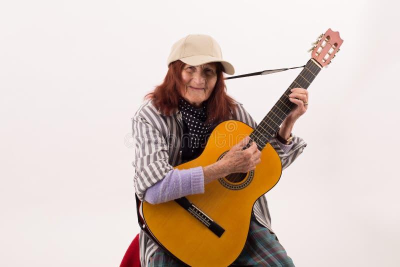 Senhora idosa engraçada que joga a guitarra acústica fotografia de stock royalty free
