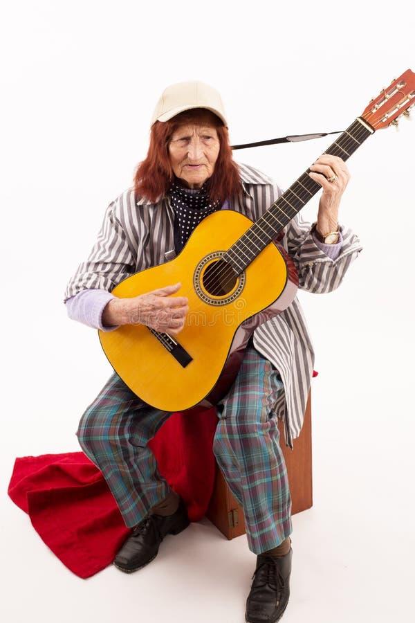 Senhora idosa engraçada que joga a guitarra acústica fotografia de stock