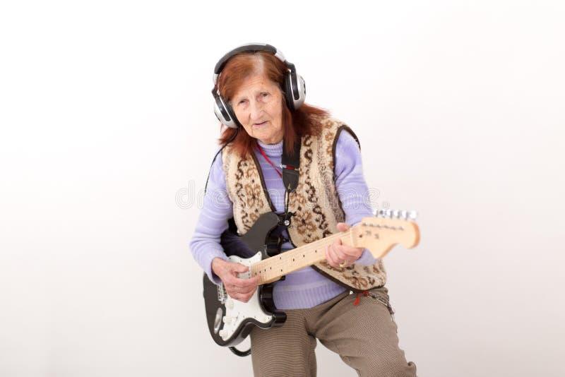 Senhora idosa engraçada que joga a guitarra elétrica imagem de stock