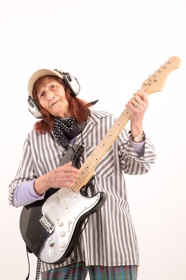 Senhora idosa engraçada que joga a guitarra elétrica imagem de stock royalty free