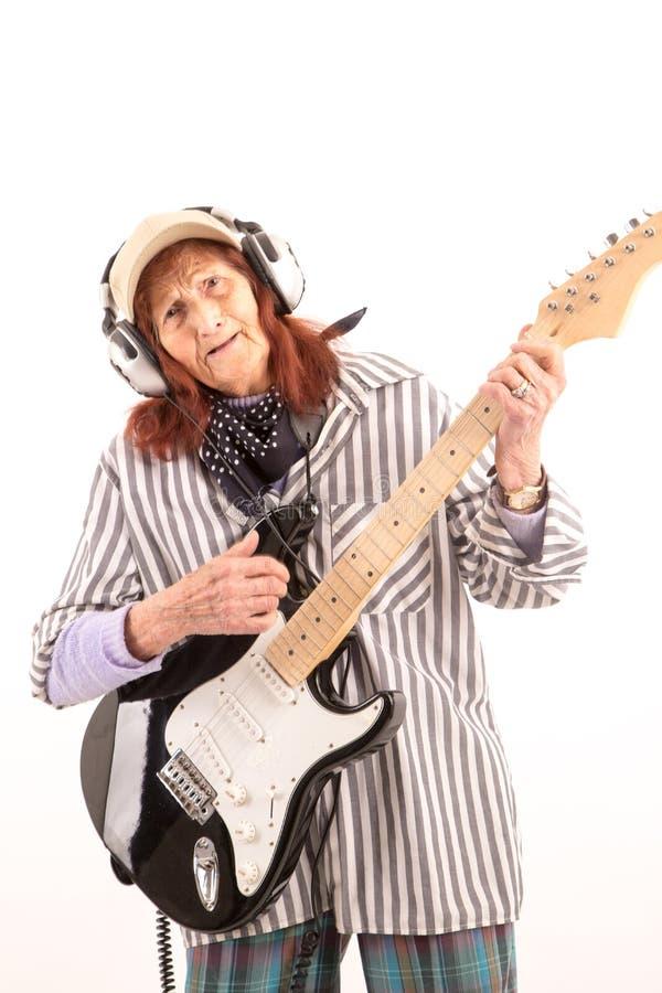 Senhora idosa engraçada que joga a guitarra elétrica foto de stock royalty free