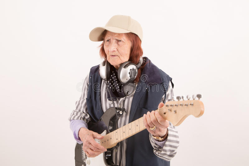 Senhora idosa engraçada que joga a guitarra elétrica fotos de stock