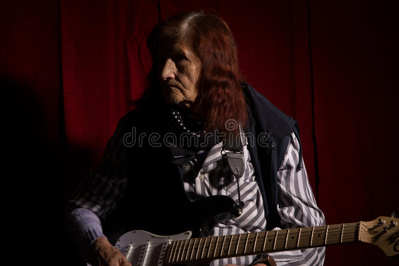 Senhora idosa engraçada que joga a guitarra elétrica imagens de stock royalty free