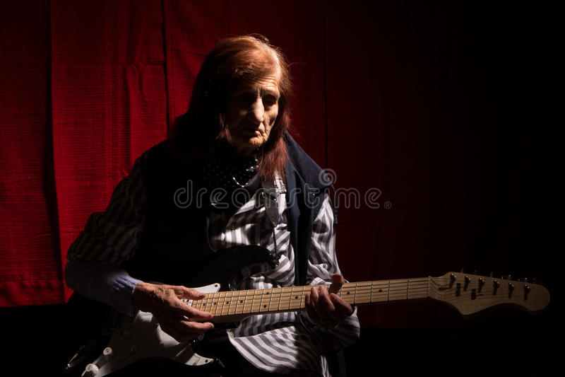 Senhora idosa engraçada que joga a guitarra elétrica foto de stock