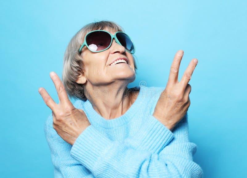 Senhora idosa engraçada que veste a camiseta, o chapéu azul e os óculos de sol mostrando o sinal da vitória fotografia de stock royalty free
