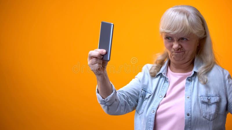 Senhora idosa feliz que toma o selfie no smartphone, careta da exibição, tecnologias modernas imagem de stock