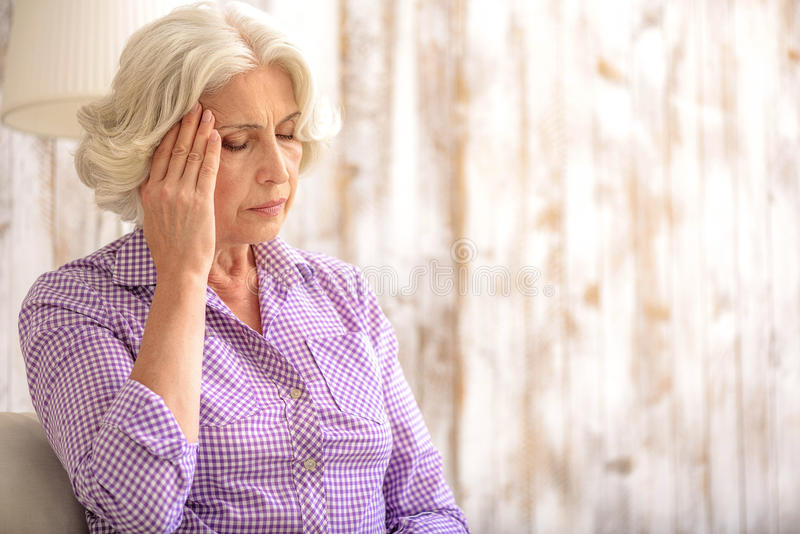A senhora idosa frustrante tem a dor na cabeça imagem de stock royalty free