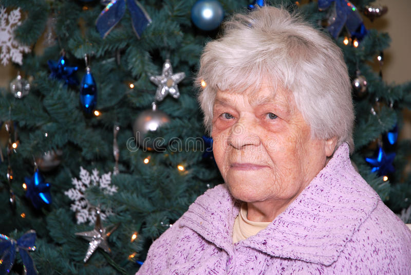 Senhora idosa na árvore de Natal fotos de stock royalty free