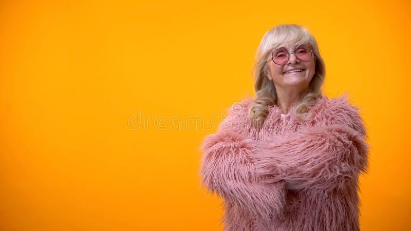 Senhora idosa positiva no revestimento cor-de-rosa e nos óculos de sol redondos que cruzam as mãos na caixa foto de stock