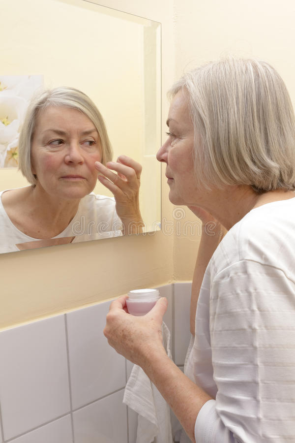 Senhora idosa que aplica a cara de creme foto de stock